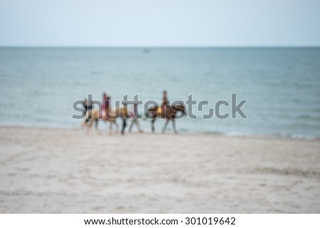 De focused or blurred image of people riding horses on the beach in the evening
