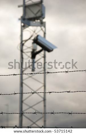 De-focused surveillance camera behind a fence with barbed wire. Focus on the fence.