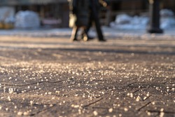 De-icing chemical reagent on the road will make the road safe in winter time. Pavement is sprinkled with technical salt, focus on foreground, people on blurred background.