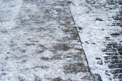 De-icing chemicals on the pavement. Pavement is sprinkled with technical salt or salt mixtures based on it, soft focus. Reagent - technical salt will make the road safe.