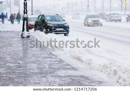 De-icing chemicals on the winter road, selective soft focus. Pavement is sprinkled with technical salt or salt mixtures based on it. Reagent - technical salt will make the road safe.Winter bad weather