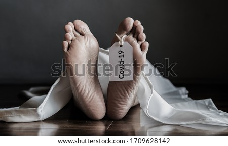 Photo of  dead body hanging tag Covid-19. senior people with coronavirus infected death at home, elderly people with congenital disease are at a higher risk of infected covid-19 disease.