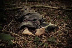 Dead body of a barefoot Caucasian boy wrapped in a blanket and abandoned on the ground in the forest