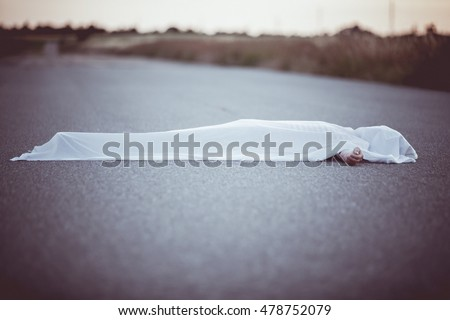Dead body with hand sticking out from under white sheet in middle of road with copy space Foto stock ©