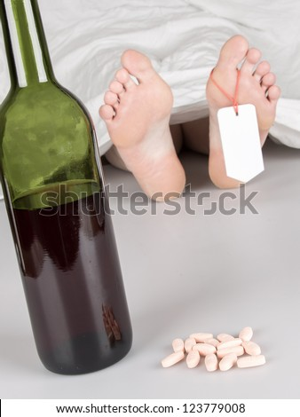 Dead body with toe tag, suicide by drug overdose and alcohol