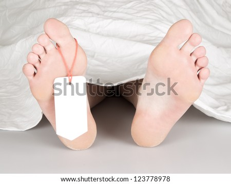 Dead body with toe tag, under a white sheet