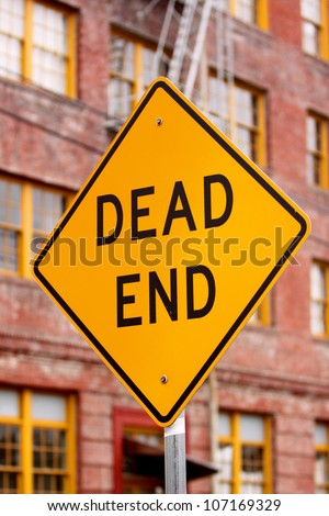 Dead end sign next to old brick building.