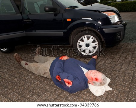 Dead or unconscious man lying next to a wrecked car