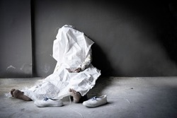 Dead person die in sitting position againt dark brown wall and concret floor with blurred shoes and bare foot was wrapped by white sack with copy space.