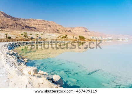 Dead Sea coastline with white salt beach and mountains at sunny day in Ein Bokek, Israel. White mineral salt shore at Dead sea, Israel. Dead sea landscape of Israel. Mineral water of Dead sea, Israel