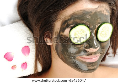 Dead Sea Mud Mask on the woman's face. Spa with vegetable and cucumber