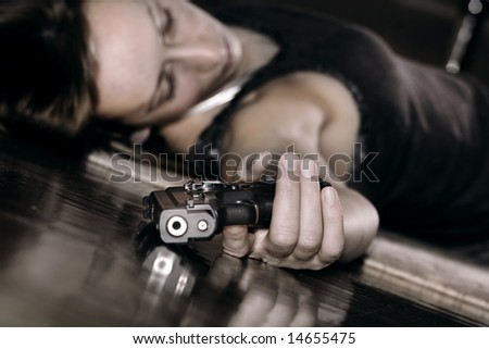 dead woman lying on the floor, gun in the hand