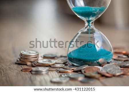 Deadline and time is money concept with hourglass and US coins currency. sandglass