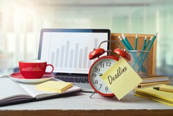 Deadline and time management concept with alarm clock on office table with computer laptop. Business background for design
