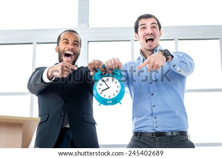 Deadline close. Two surprised businessman holding clock alarm clock in his hands and shout loudly pointing the finger at a time. Businessman dressed in formal wear