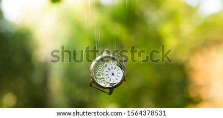 deadline extended graphic design concept picture of hand clock motion falling effect in air on blurred unfocused green yellow natural bokeh background
