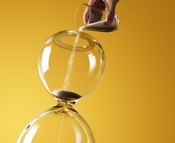 Deadline extended represented by pouring more sand into hourglass