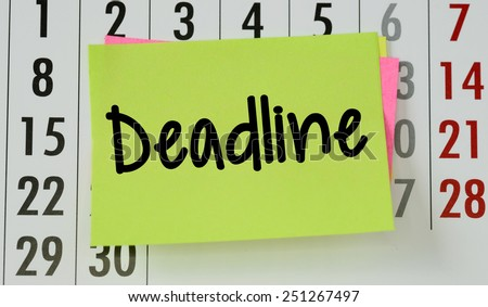 Deadline on calendar background. The phrase Deadline on sticky paper note stuck to a wall calendar background