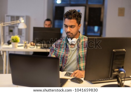 deadline, technology and people concept - creative man with laptop computer working at night office