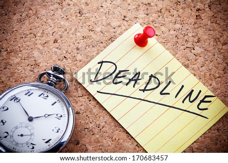 Deadline word written on a post note and hanged on the cork-board with an old pocket watch.