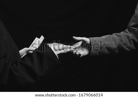 Deal. Arm transfer of money. Currency transfer on black background. Black and white photo. Dollars transfer   Foto d'archivio ©