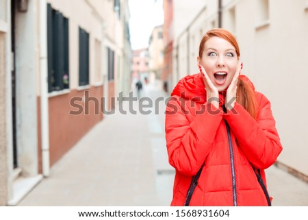 Deal or sale, shocking news. Shocked woman in Murano, Venice, Italy. Irish model in red winter coat clothing, redhead hair standing on urban background. Amazed, stunned, emotion, expression concept.