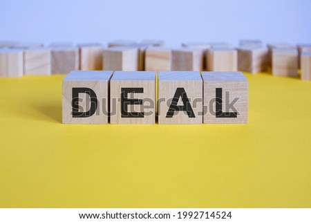 deal word on wooden building blocks lying on the yellow table, concept