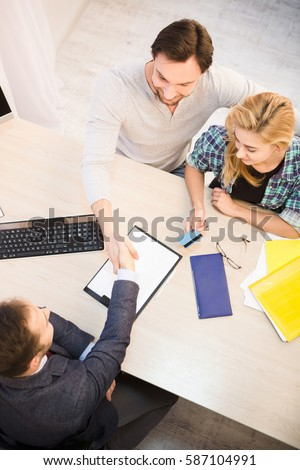 Dealership concept. Bank concept. Money concept. Top toned of sales manager shaking hand to customer after signing agreement or contract for getting credit card.