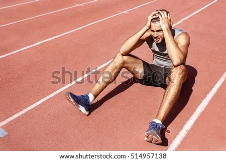Dealing with the loss. Young male athlete looking upset and disappointed after losing the race sitting on the racetrack with his hands to his head copyspace Foto d'archivio ©