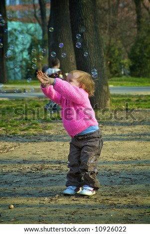 Dear girl plays with the soap bubbles