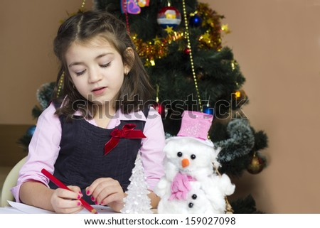 Dear Santa ... Beautiful little girl writes letter to Santa Claus in festively decorated room