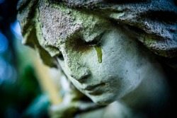 Death concept. Close Up of ancient stone statue of crying sad angel with tears in face as symbol of end of human life.