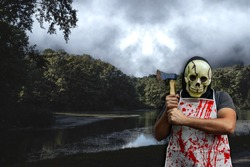 Death Halloween horror costume. Man with skeleton mask, bloody apron and axe on a creepy forest's lake.