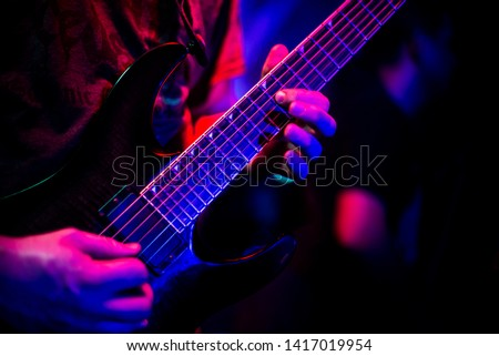 Death Metal guitarist during playing solo in dimmed, coloured lighting.