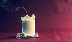 Death symbolism - Candle blown by wind and smoke on dark cardinal red colour background