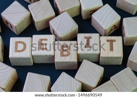 Debit, money or cash that people can pay to buy consume product concept, cube wooden block with alphabet combine the word Debit on black chalkboard background.