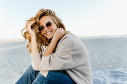 Debonair blonde girl sitting at sandy beach in autumn morning. Outdoor portrait of pretty curly woman smiling on sea background