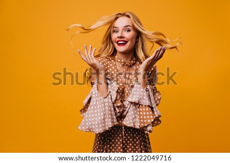 Debonair female model in vintage blouse expressing amazement. Indoor photo of positive girl posing with surprised smile on yellow background. #1222049716