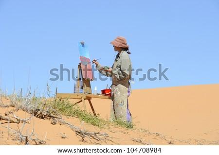 Debra Hilditch, landscape painter at work on location in the Kalahari desert,South Africa