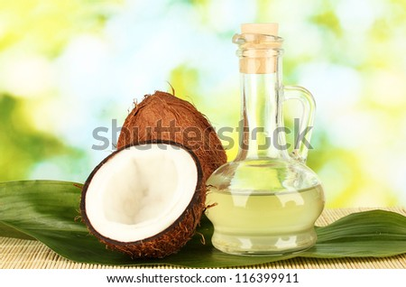 decanter with coconut oil and coconuts on green background