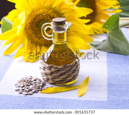 Decanter with sunflower oil. Flowers with a bottle of sunflower oil. Small bottle with sunflower oil and purified seeds.