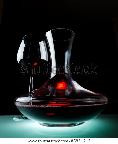 Decanting of red wine. Black background.