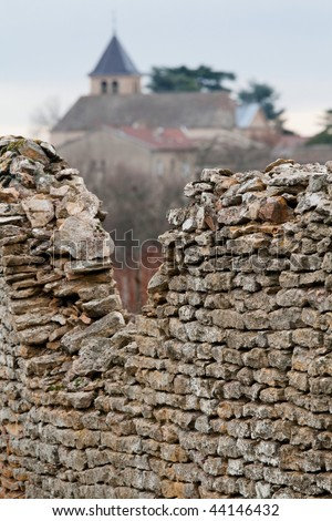 Decayed ancient stone wall constructed around old vineyard and village in Burgundy, France.
