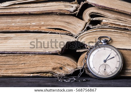 Decaying clock on the background of old shabby wise books. #568756867