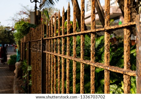 Decaying fence which is covered by rust. Fence of a garden which is near to sea coast.