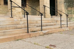 Decaying limestone stairs and columns of an old church entry, black railings and patchwork, horizontal aspect