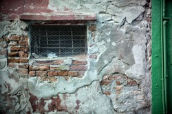 Decaying red wall with visible bricks and concrete patches, small window with metal net and green wall on the right