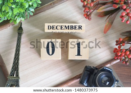 December 1. Date of December month. Number Cube with a flower camera and Sign wood on Diamond wood table for the background.