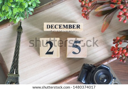 December 25. Date of December month. Number Cube with a flower camera and Sign wood on Diamond wood table for the background.