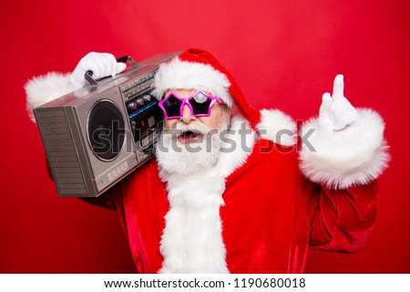 December noel eve winter wish christmastime choice choose. Stylish white beard aged Santa in spectacles costume hat indicate show point up listen radio audio sound isolated on red background #1190680018